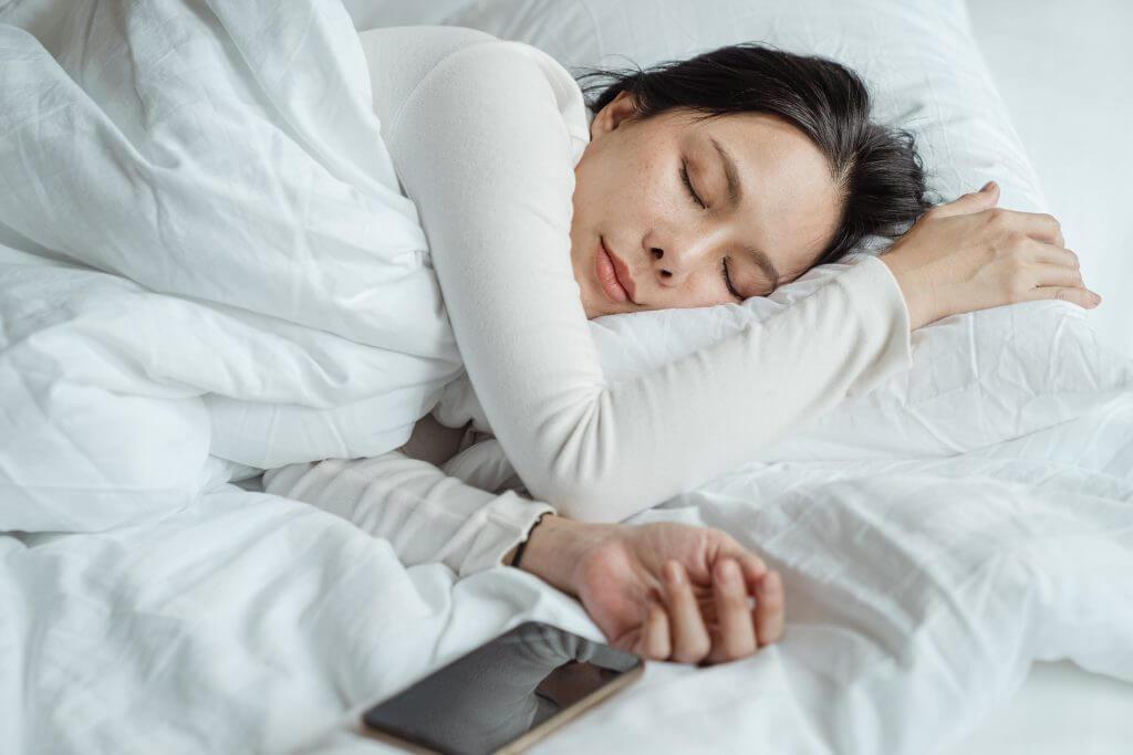 women sleeping on side in bed